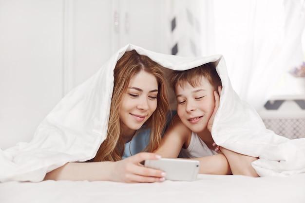Una hermosa joven y su alegre hermano menor miran fotos en su teléfono mientras están acostados en la cama con una sonrisa