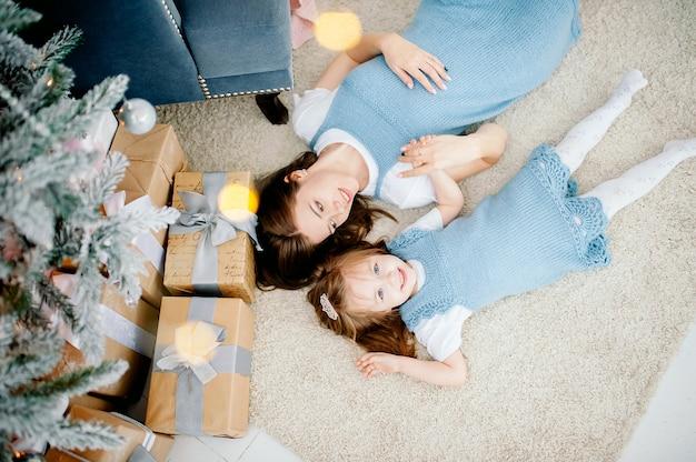 Hermosa joven y su encantadora hijita se abrazan en los mismos trajes sonriendo. navidad