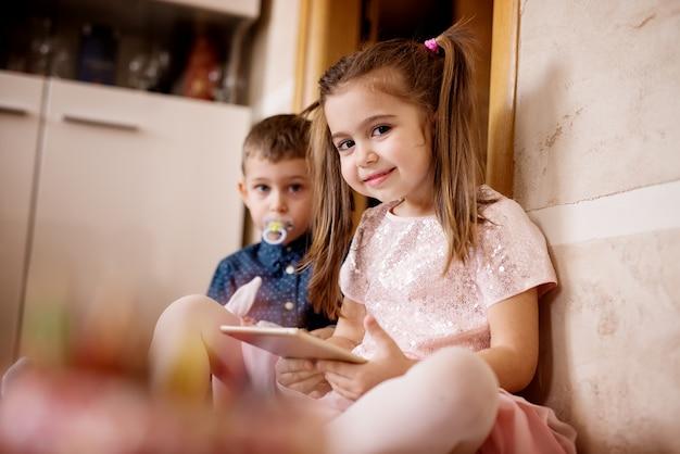 Hermosa joven y su hermanito, jugando juegos de tableta en el piso.