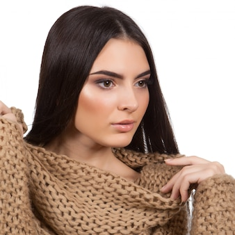 Hermosa joven en suéter de invierno sobre un fondo blanco.