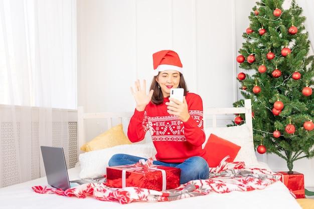 Una hermosa joven con un suéter rojo está hablando por teléfono con un regalo en casa