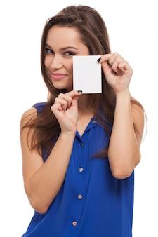 Hermosa joven tiene tarjeta en blanco