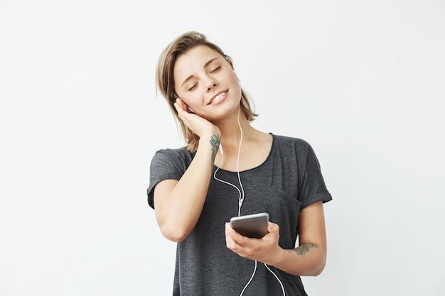Hermosa joven tierna sonriente escuchando música en auriculares con los ojos cerrados.