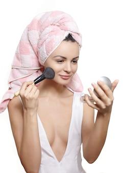 Hermosa joven en toalla en la cabeza aplicando maquillaje en el espejo