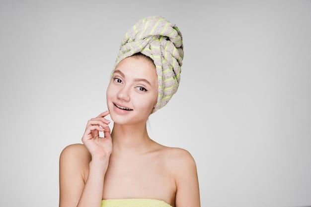 Hermosa joven con una toalla en la cabeza sonriendo, pensando en la belleza, spa de día
