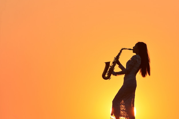 Hermosa joven tocando el saxofón durante la puesta de sol, tailandia