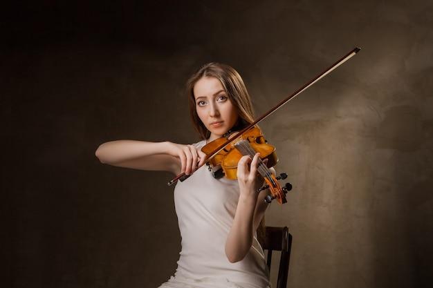 Hermosa joven tocando el violín sobre fondo negro