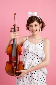 Hermosa joven tocando el violín sobre rosa