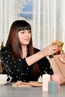 Hermosa joven tomando una caja de regalo de una bolsa de papel sentado en una mesa sobre un fondo desenfocado.