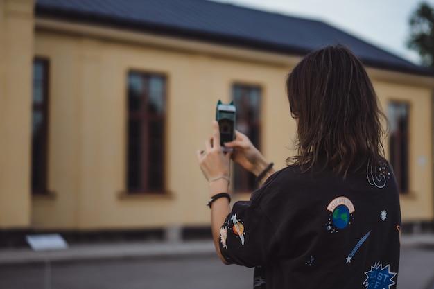 Hermosa joven tomando fotos en un teléfono inteligente