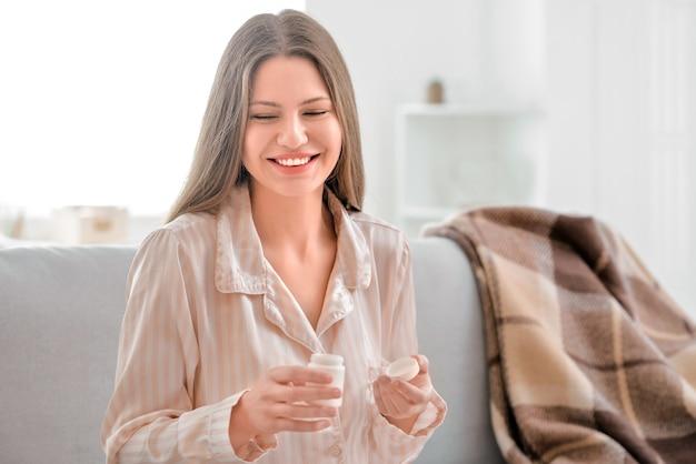 Hermosa joven tomando pastillas en casa