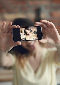Hermosa joven tomando selfie con smartphone