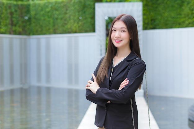 Hermosa joven trabajadora profesional asiática en traje negro con los brazos cruzados y mira a la cámara. ella sonríe feliz mientras camina al aire libre para trabajar en la oficina en el parque de la ciudad.