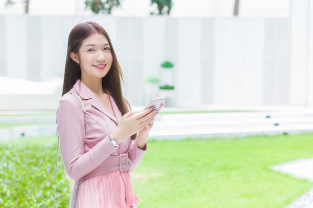 Hermosa joven trabajadora profesional asiática en traje rosa tiene smartphone y mira a la cámara. ella sonríe feliz mientras camina al aire libre para trabajar en la oficina en el centro del parque de la ciudad