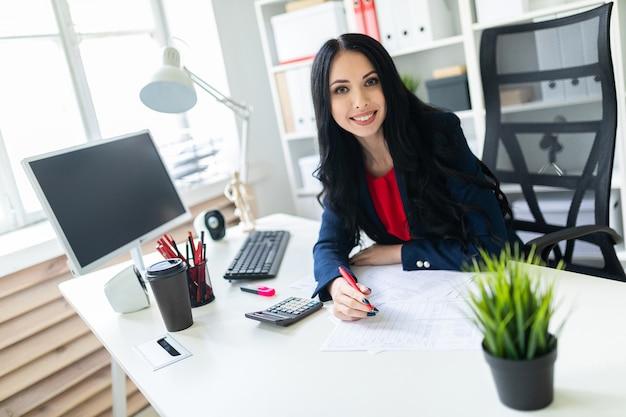 Hermosa joven trabajando con calculadora y documentos en la oficina en la mesa