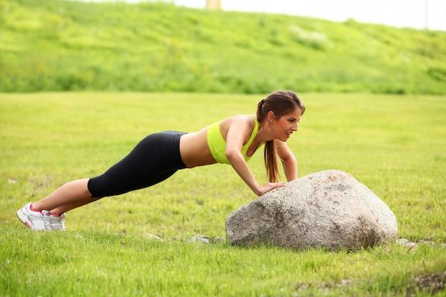 Hermosa joven trabajando cerca de piedra