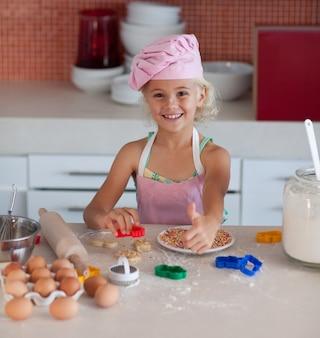 Hermosa joven trabajando en la cocina pulgar arriba