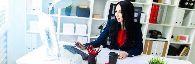 Hermosa joven trabajando con la computadora y documentos en la oficina en la mesa.
