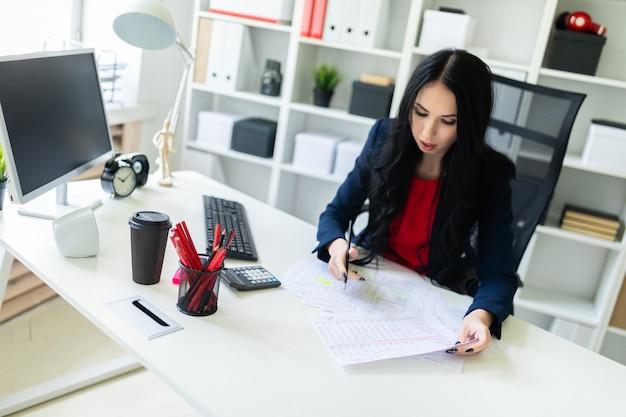 Hermosa joven está trabajando con documentos en la oficina en la mesa y está sosteniendo un lápiz en la mano.