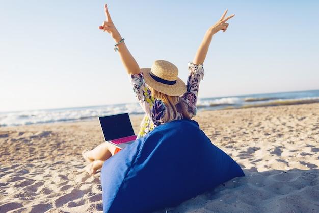 Hermosa joven trabajando con un portátil en la playa tropical