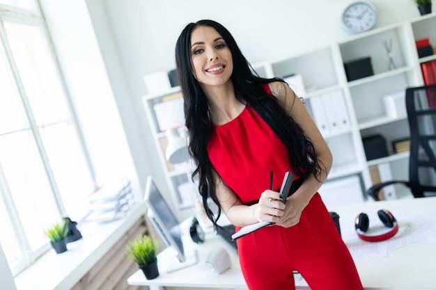 Hermosa joven en un traje rojo está de pie en la oficina y sosteniendo un cuaderno y un lápiz.