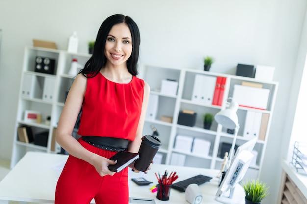 Hermosa joven en un traje rojo está de pie en la oficina y está sosteniendo un cuaderno y un vaso de café.