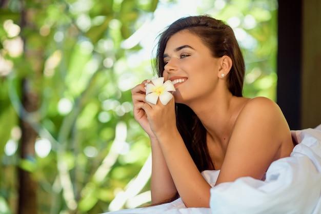 Hermosa joven tumbado en la mesa de masaje en el salón de spa