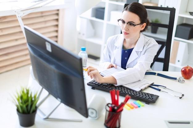 Una hermosa joven con una túnica blanca está sentada en un escritorio de la computadora con documentos y una pluma en sus manos.