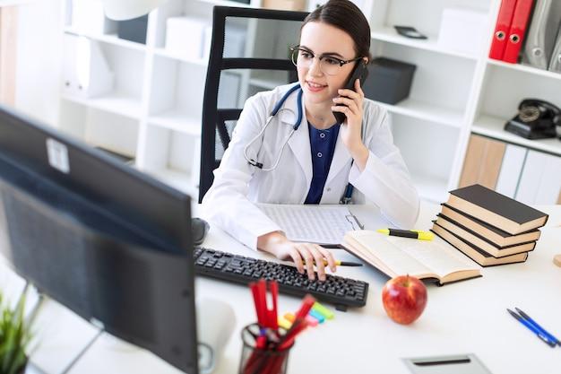 Una hermosa joven con una túnica blanca está sentada a la mesa, hablando por teléfono y sosteniendo su mano en el teclado.