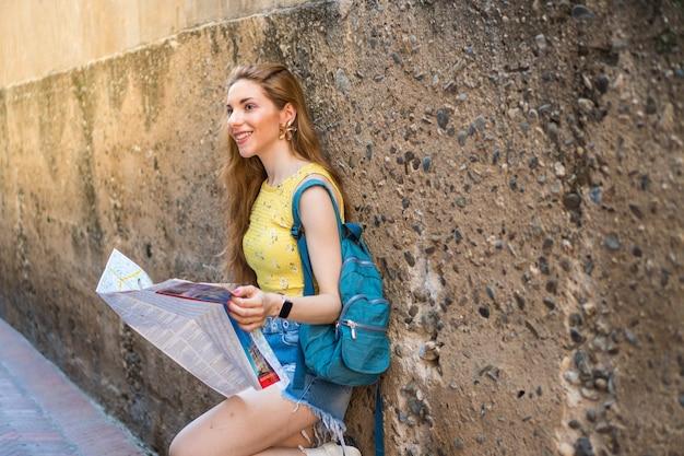 Hermosa joven de turismo con un mapa chica en vacaciones de verano en sevilla españa