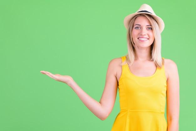 Hermosa joven turista con cabello rubio en clave de croma en verde