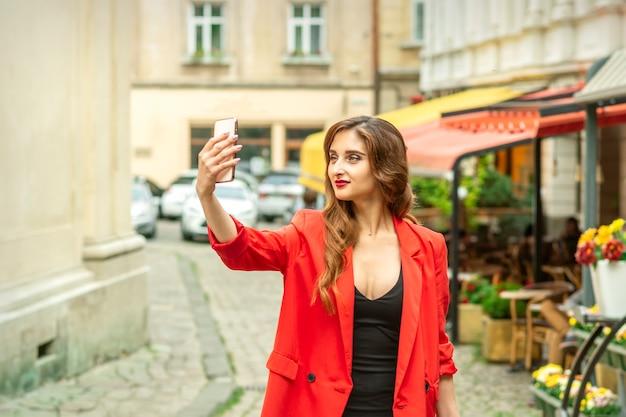 Hermosa joven turista caucásica toma un selfie en una ciudad europea
