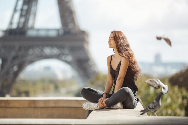 Hermosa joven turista cerca de la torre eiffel, en parís.