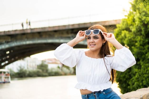 Una hermosa joven turista disfrutando de la vista del río durante sus vacaciones de verano.