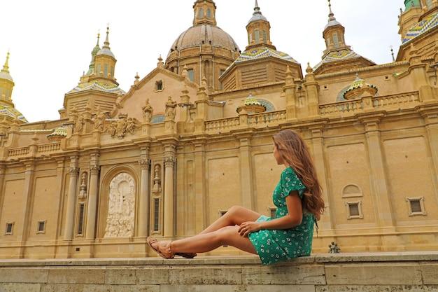 Hermosa joven turista mujer sentada en la pared mirando la basílica de zaragoza, españa