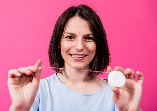 Hermosa joven usa hilo dental sobre fondo rosa