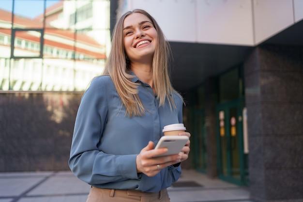Hermosa joven está usando una aplicación en su dispositivo de teléfono inteligente para enviar un mensaje de texto cerca de edificios comerciales
