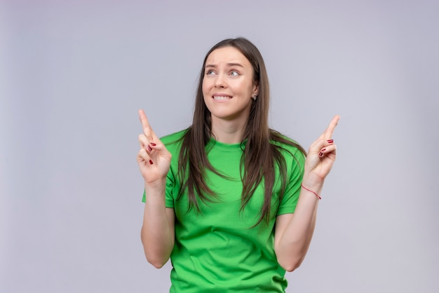 Hermosa joven vestida con camiseta verde haciendo deseable con cruzar los dedos con expresión de esperanza de pie sobre fondo blanco aislado