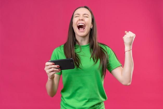 Hermosa joven vestida con camiseta verde con smartphone loco feliz levantando el puño cerrado sonriendo alegremente regocijándose de su éxito de pie sobre fondo rosa aislado