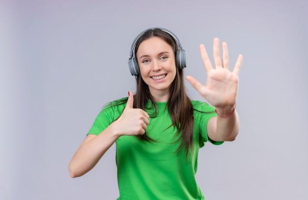 Hermosa joven vestida con camiseta verde sonriendo alegremente mostrando y apuntando hacia arriba con los dedos número cinco y pulgares arriba sonriendo alegremente de pie sobre fondo blanco aislado