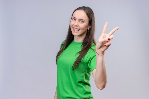 Hermosa joven vestida con camiseta verde sonriendo alegremente mostrando y apuntando hacia arriba con los dedos número dos o el signo de la victoria de pie sobre fondo blanco aislado