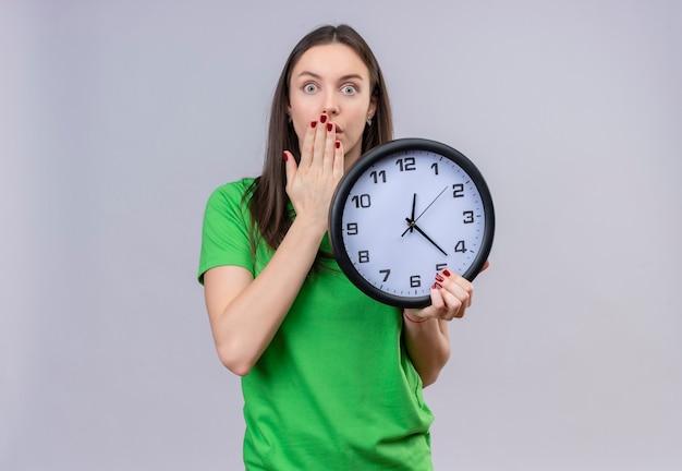 Hermosa joven vestida con camiseta verde sosteniendo el reloj mirando sorprendido y conmocionado cubriendo la boca con la mano de pie sobre fondo blanco aislado