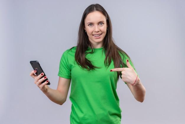 Hermosa joven vestida con camiseta verde sosteniendo smartphone sonriendo apuntando con el dedo a él de pie sobre fondo blanco aislado