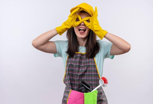 Hermosa joven vestida con delantal, gorra y guantes de goma haciendo bien los signos como binoculares con los dedos mirando a través de los dedos sacando la lengua
