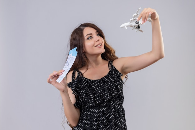 Hermosa joven vestida de lunares sosteniendo boletos de avión y avión de juguete sonriendo alegremente mirando juguetón y feliz de pie sobre fondo blanco