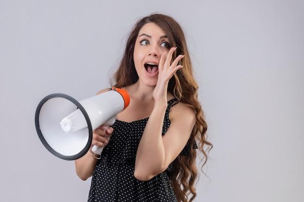 Hermosa joven vestida de lunares sosteniendo megáfono gritando con la mano cerca de la boca sobre fondo blanco.