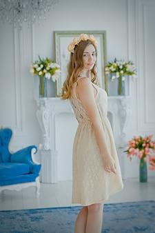 Hermosa joven en vestido ligero y corona de rosas en la cabeza