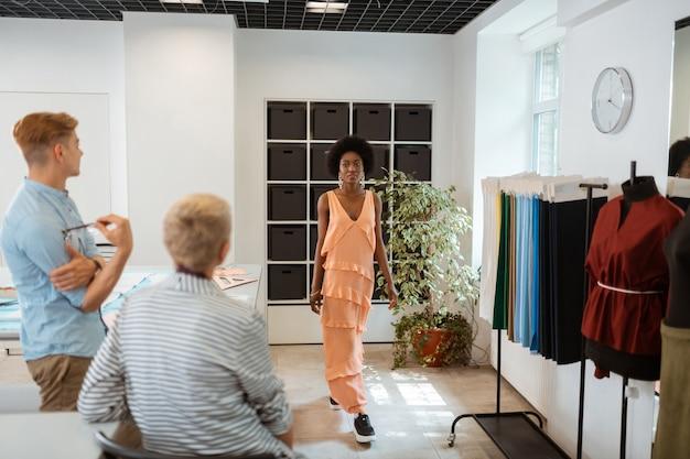 Hermosa joven con un vestido naranja de moda en un taller frente a sus compañeros de trabajo