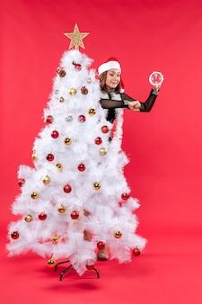 Hermosa joven en un vestido negro con sombrero de santa claus escondido detrás del árbol de navidad y sosteniendo el reloj comprobando el tiempo