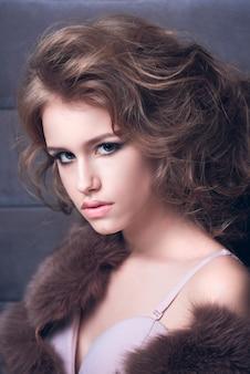 Hermosa joven en un vestido de noche y un abrigo de piel
